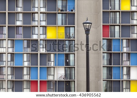 Colored windows with street lamp. Urban scene featuring modernist and brutalist apartment complex build in 1973. - stock photo