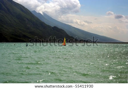 Colored windsurfer on a lake with mountains and sky as a background - stock photo