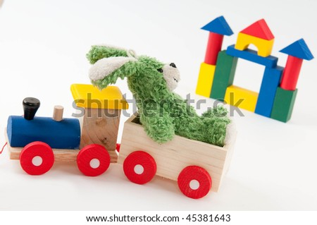 Colored wooden toy train with green toy hair and wooden toy castle on white background - stock photo