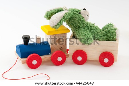 colored wooden toy train with green toy hair on white background - stock photo
