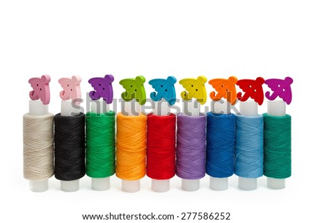 Colored yarn and wooden buttons-umbrellas - stock photo