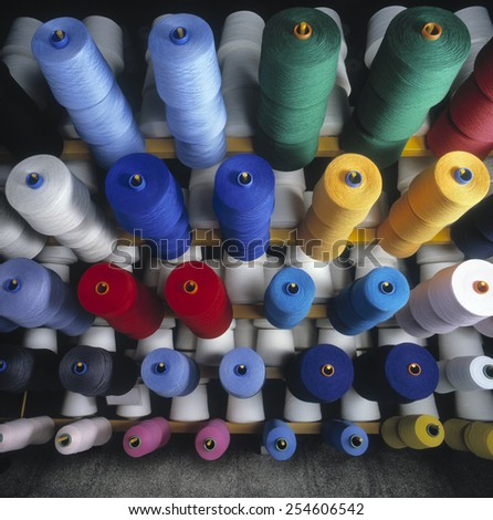 Colored yarn bobbins in textile industry. - stock photo