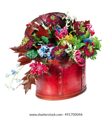 Colorful abstract floral arrangement of roses, lilies, irises and maple leaves in red leather bag isolated on white background.