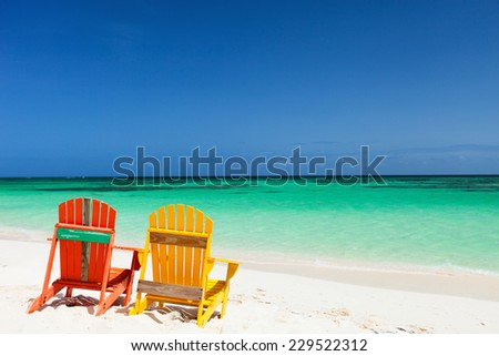Colorful adirondack yellow and orange lounge chairs at tropical beach in Caribbean with beautiful turquoise ocean water, white sand and blue sky - stock photo