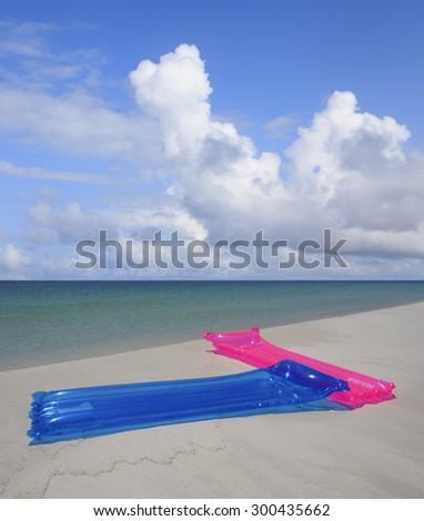 Colorful Air Mattresses on White Sand Florida Beach - stock photo