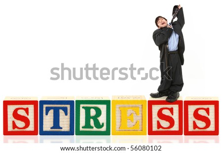 Colorful alphabet blocks spelling the word STRESS with adorable boy in large suit standing on top.