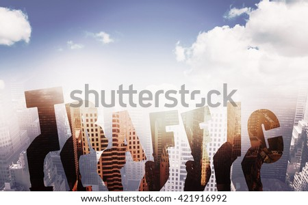 Colorful alphabet spelling traffic held up by people against aerial view of a city on a cloudy day - stock photo