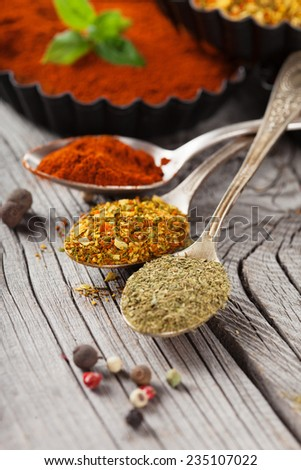 Colorful aromatic spices and herbs on old wooden background, selective focus - stock photo