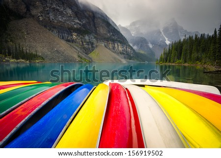 Colorful array of canoes on the shoreline of Lake Moraine in Alberta, Canada on a gloomy morning - stock photo