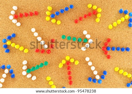 colorful arrows with random pined on cork board - stock photo