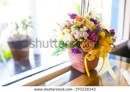 Colorful artificial flower decoration, in a cafe restaurant. - stock photo