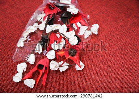 Colorful artificial flower made with paper,thermocol and bamboo leaves on red jute textile background.Colorful decoration artificial flower (vintage) can be put in a flower vase - stock photo