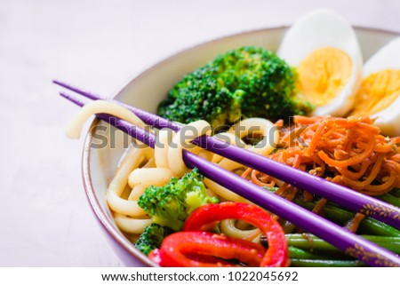 Colorful Asian bowl with udon noodles, vegetables and egg, selective focus