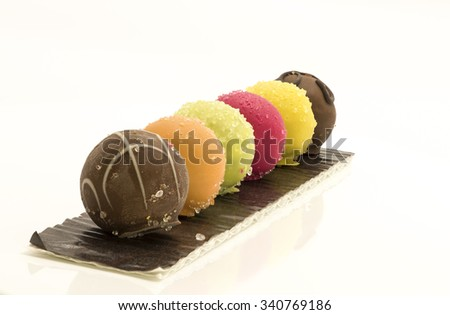 Colorful assortment of chocolate balls in a row on long brown paper card.  Different colors for variety of fruits flavor and coated with white sugar crystals. Isolated on white background. - stock photo