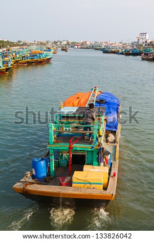 colorful authentic Fishing boats in the bay in Vietnam against the blue sky - stock photo