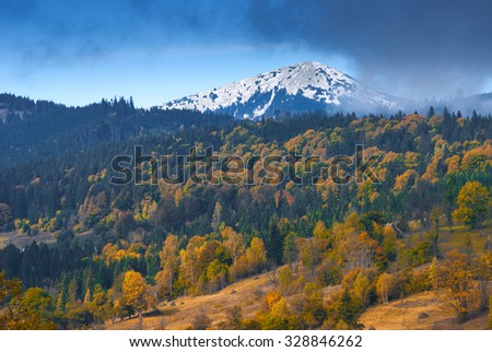 Colorful autumn forest on a Carpathian hill with snow-capped mountain peaks on a skyline - stock photo