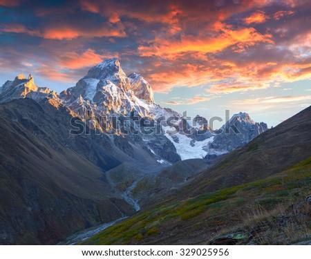Colorful autumn sunrise in the Caucasus mountains. Upper Svaneti, Main Caucasus ridge, Georgia, Europe. October 2015. - stock photo