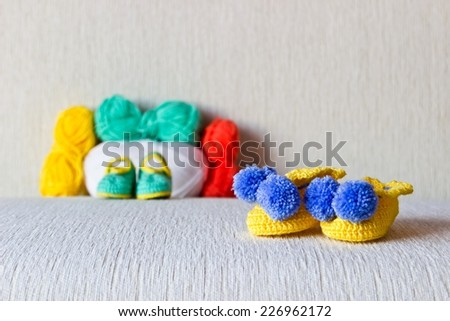 Colorful baby bootees with colored wool on white background
