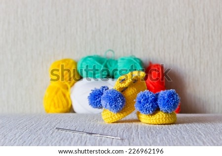 Colorful baby shoes with wool and knitting needles on white background close up - stock photo