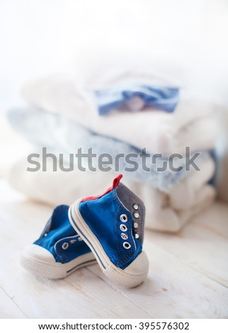 Colorful   baby  sneakers on wooden background - stock photo