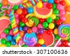 Colorful background of assorted candies including gum balls, lollipops and jelly candies - stock photo