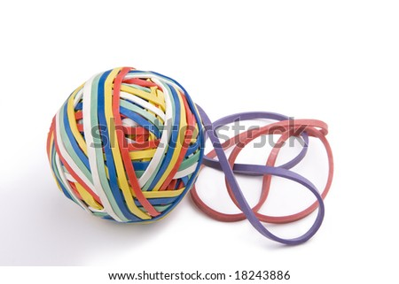 Colorful ball of rubber bands and two loose rubberbands on the side.  On a white background. - stock photo