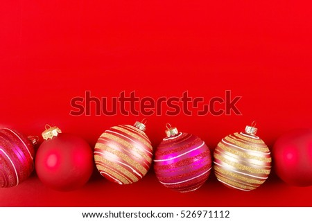 Colorful ball shaped Christmas decorations in row on red background.