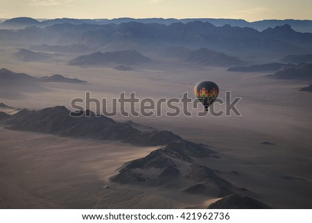 Colorful ballon flying over the beautiful mountain terrain. High altitude. Early morning. (Namibia, South Africa)