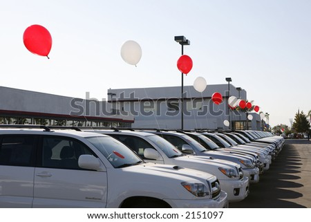 Colorful balloons entice car buyers to stop and look - stock photo