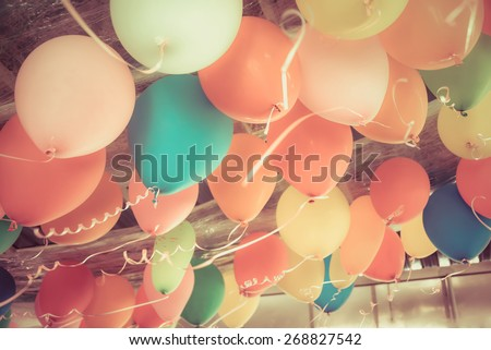 Colorful balloons floating on the ceiling of a kid party celebration in vintage retro color style - stock photo