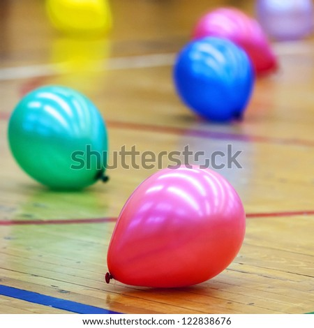 Colorful balloons on wooden floor of sports hall - stock photo