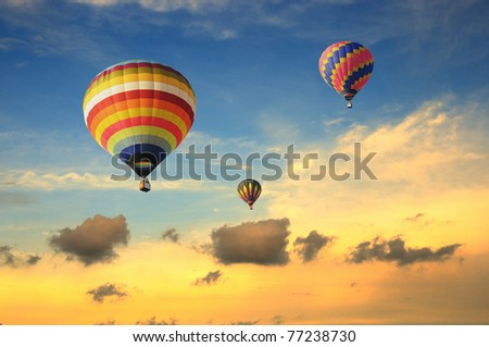 Colorful balloons rising up during sunset - stock photo