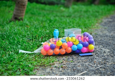 Colorful balls in net bag with toys prepared for kids games - stock photo