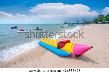 Colorful banana boat and Jetski on the beach of holiday season,pattaya beach,the most famous beach in thailand - stock photo