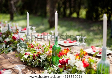 Colorful banquet table in spring garden - stock photo