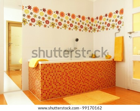 Colorful bathroom with orange mosaic bathtub and yellow towels - stock photo