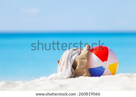 colorful beach ball and beach accessories at the perfect tropical beach - stock photo