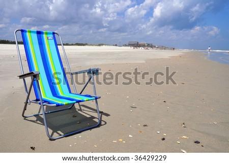 colorful beach chair on sandy beach. - stock photo