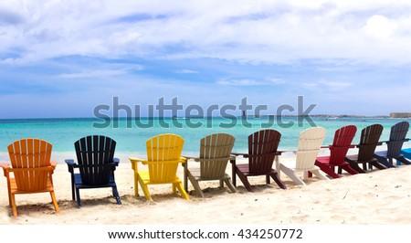 colorful beach chairs on caribbean coast - stock photo