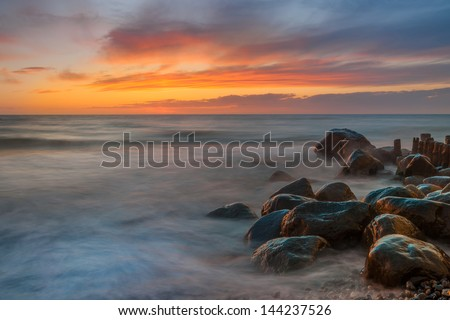 Colorful beach sunset with blurred water and wet reflecting stones. - stock photo