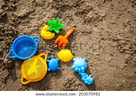 colorful beach toys for kids in sand - stock photo