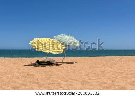Colorful beach umbrellas on the sandy beach on summer day.  - stock photo