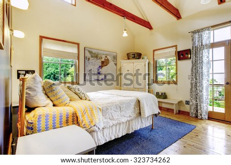 Colorful bedroom with hardwood floor and blue interior decor. - stock photo