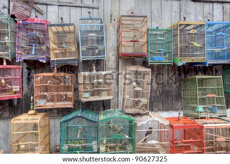 Colorful Bird Cages hanging on a wall in outdoor market - stock photo