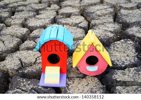 colorful bird house on crack soil. - stock photo
