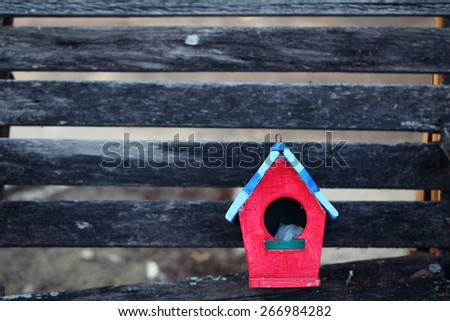 colorful bird house on wooden panel - stock photo