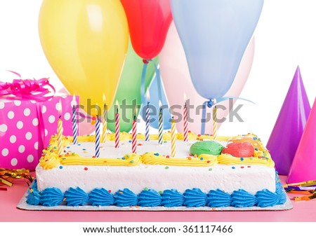 Colorful birthday cake and burning candles with decorations on a white background - stock photo