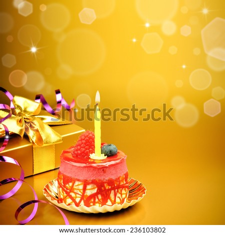 Colorful birthday cake with candle on golden background - stock photo