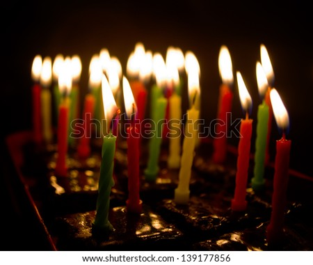 Colorful birthday candles burning on chocolate muffins over black background with shallow depth of field - stock photo