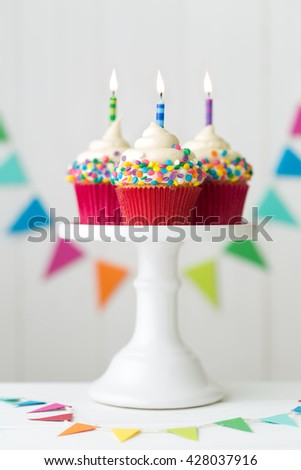Colorful birthday cupcakes on a cake stand - stock photo